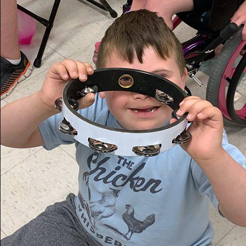 A young boy looks through a tamborine