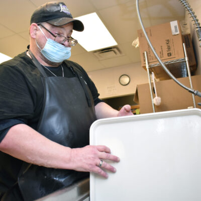 A man with a facemask, glasses and baseball hat washes a large tray