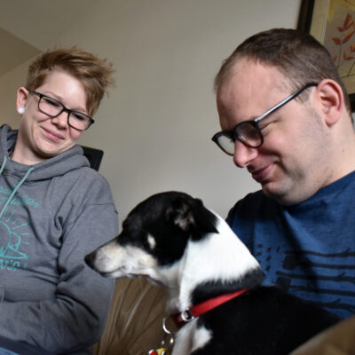 A man holds a small dog while a woman looks on