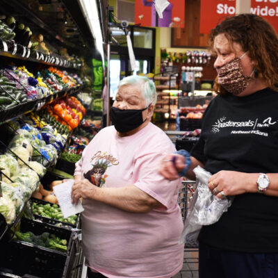 Two women select produce at a grocery store