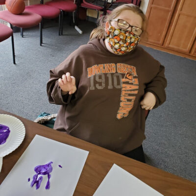 A young woman in face mask makes a painted hand print