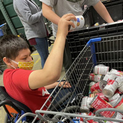 A teen boy in a wheelchair hands canned goods from a cart to another person