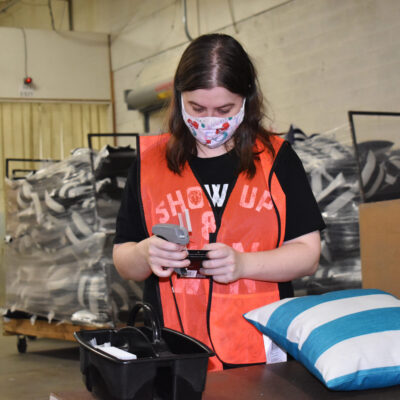 A young woman in face mask scans a tag for a pillow