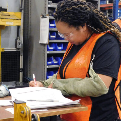 A young black woman does paperwork in a factory