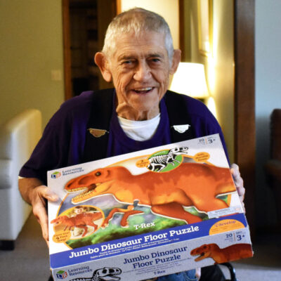 A senior man smiles and holds up a dinosaur puzzle box