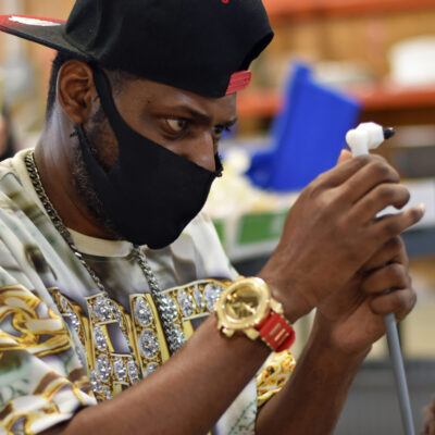 A young Black man wearing a face mask focuses on a task