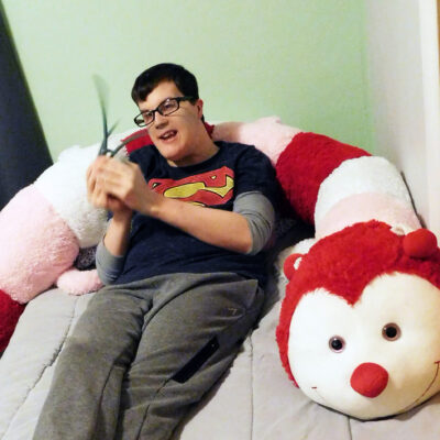 A young man lounges on a bed with a giant stuffed caterpillar