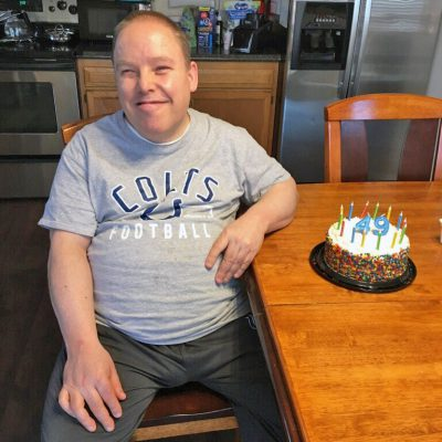 A man smiles next to a birthday cake