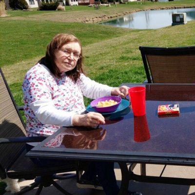 A woman eats a meal at a backyard patio table