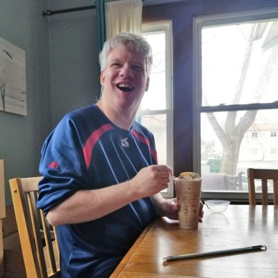 A man smiles while enjoying a frozen coffee drink