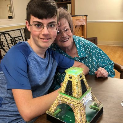 A young man and a senior woman smile together with a model of the Eiffel Tower