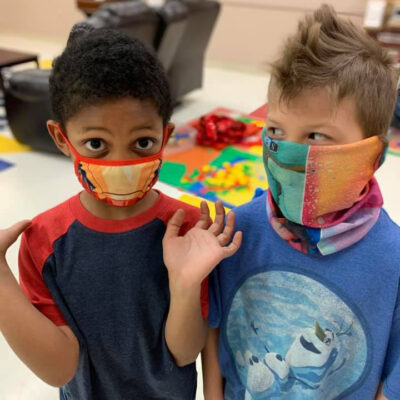 A young boy wearing a face mask glances at another young boy in face mask
