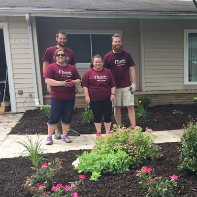 Four volunteers in Lincoln Financial T-shirts pose by landscaping