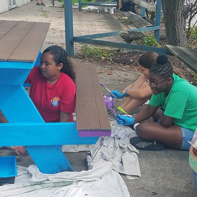 Three girls paint a picnic table
