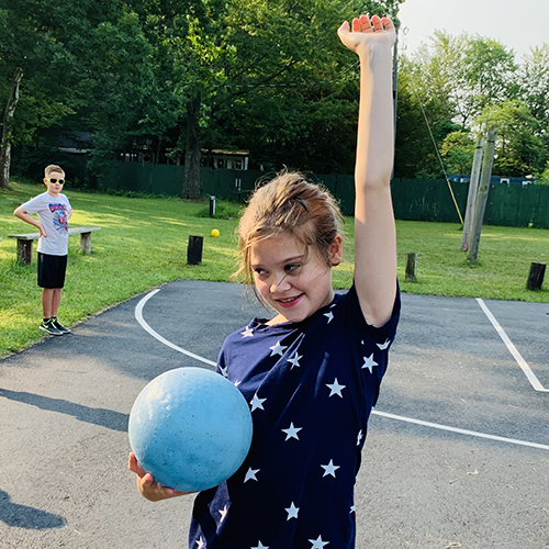 A young girl stands on a playground with one hand in the air and a ball in the other hand