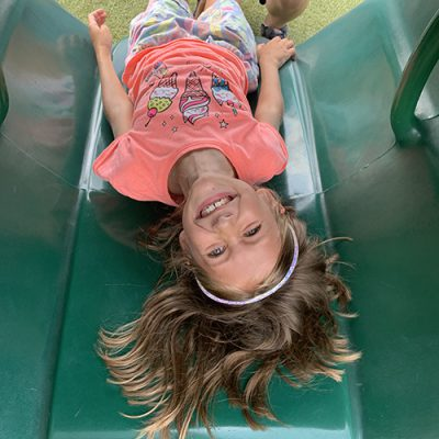 Upside down view of girl in playground tunnel